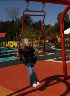 Girl in accessible hand-powered swing