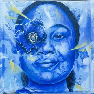 Within the mural, a close-up of a woman's face with a flower over her left eye