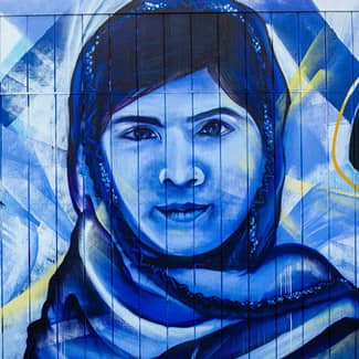A close-up of Malala Yousafzai, and to her right, a large hummingbird.