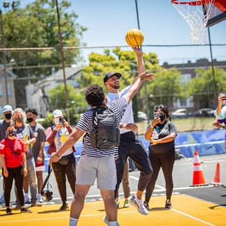 Stephen Curry tests the new basketball court with a layup alongisde a Franklin student